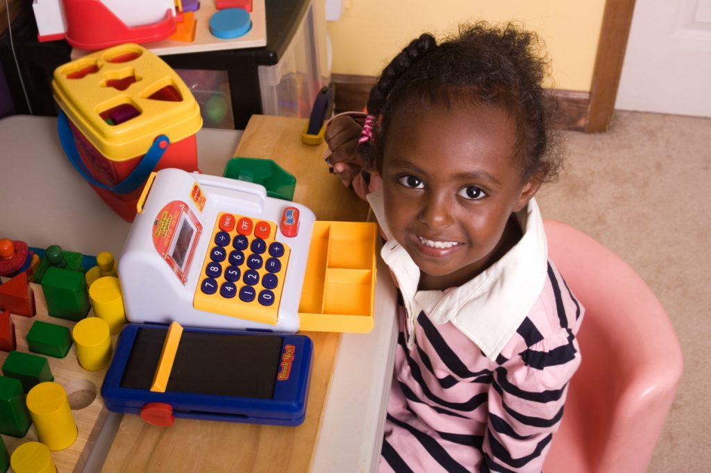 Happy girl learning about finance with toy cash register