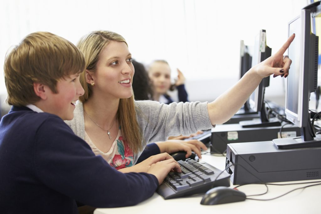 Teacher And Pupil In School Computer Class Working On Spreadsheets