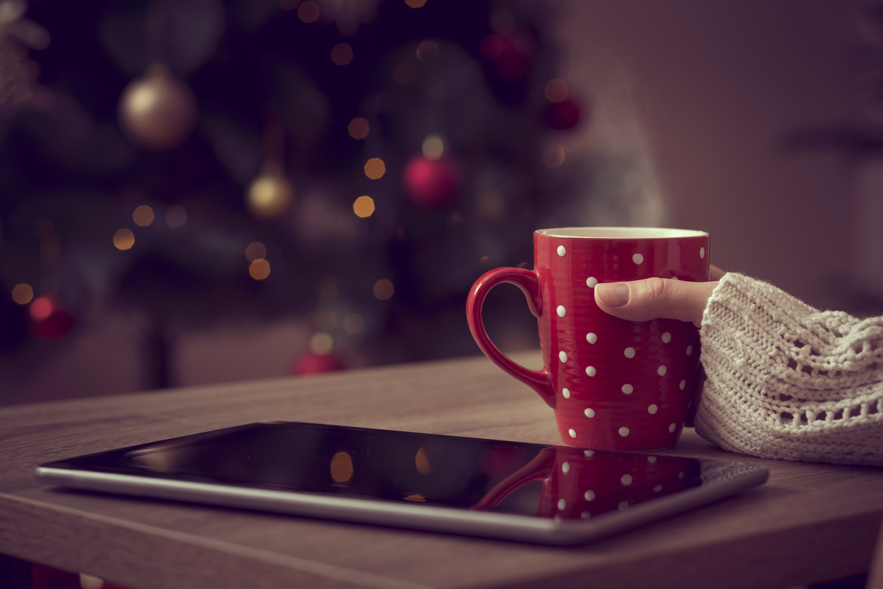 Close up of female hand holding a cup of hot coffee with tablet computer set next to it and christmas tree in the background